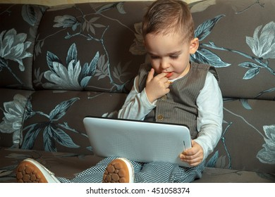 young boy with finger in his mouth watching something on a mobile tablet and sits on a couch