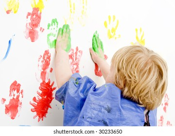 Young boy finger painting on a wall