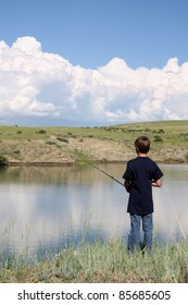 Young boy fishing at the edge of a pond with beautiful blue sky.