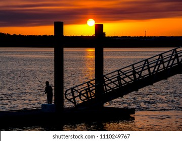 A young boy fishing on a floating dock as the sunsets over the Guana River near St. Augustine, Florida.