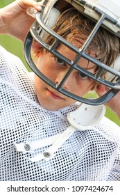Young boy in a football uniform taking off his helmet after a game