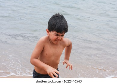 Young boy forwns and runs away from waves on sea shore