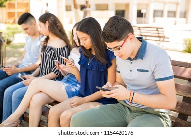 Young boy with friends using smart phones sitting on bench outdoors