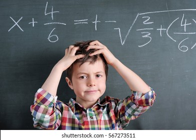 Young boy in front of blackboard with mathematical problem grabbing his hair