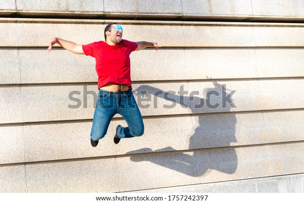 young boy of generation Y in flight during a jump, creative and inappropriate use of protective masks, a symbol of optimism and positivity for the future by the younger generations