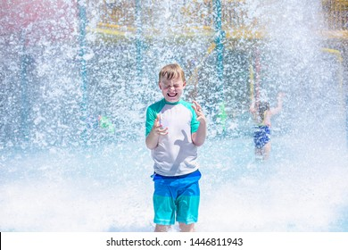 Young boy getting soaking wet while at an outdoor water park. Lots of water splashing water behind the boy. He is smiling and anticipating getting wet and drenched