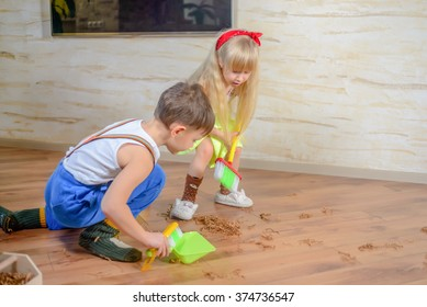 Young boy and girl helping to clean house using colorful green pans and brushes as they sweep up wood shavings and dirt off a wooden parquet floor