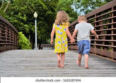 Young boy and girl holding hands walking on bridge