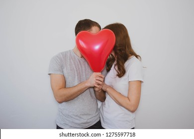 young boy and girl kissing and holding a heart-shaped balloon in front of them, burying their faces against a white background, Valentine's Day