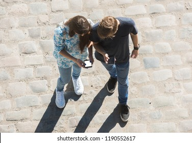 Young boy and girl look at mobile phone n the street. View from above.