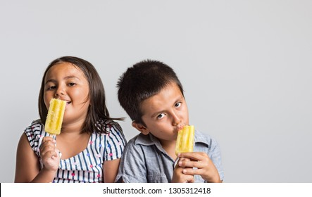 Young boy and girl with natural expression enjoying ice cream, studio image with copy space for text.