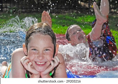 Young boy and girl in outdoor waterplay on slippery slide