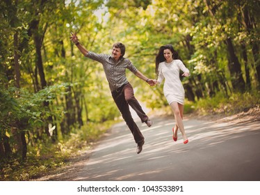 Young boy and girl are running along the road and jumping up fun. The newlyweds laugh happily. Hooray concept. Hippie couple.