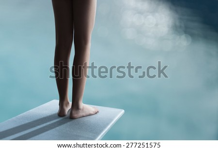 Young boy or girl is standing on a divingboard