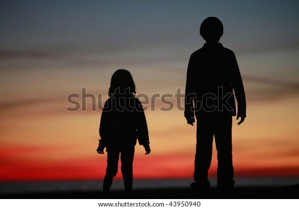 Young Boy and Girl Standing in Silhouette against colorful Sunset