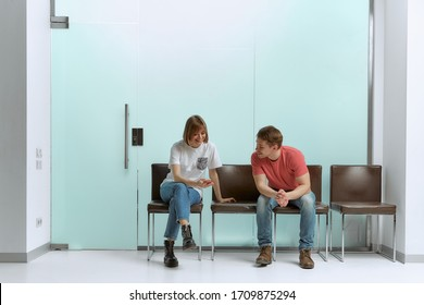 A young boy and girl are waiting in line to see a doctor in a hospital and watch the news on their smartphones.