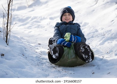 Young the boy goes down the snow-covered hill on a plastic bag.