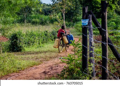 A young boy going to get some water from a nearby well. He is using a too big bike carrying too many canisters but he is still managing to get the water for his family. Near Mbale in Uganda