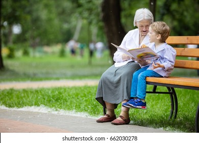 Young boy and great grandmother reading book in summer park, grandson laughing and eating bun