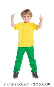 Young boy in green pants holds his thumbs up on the white background
