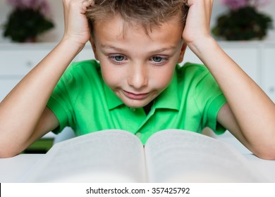 Young boy in green polo shirt having serious learning difficulties while trying to read a textbook from school.