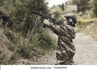 Young boy with a gun, laser tag, war simulation. Lasertag shooting game. Military sport