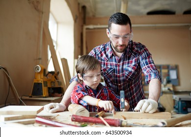 Young boy hammering nail into wooden plank