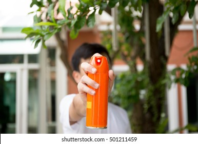 Young boy hand holding insect spray can outdoor
