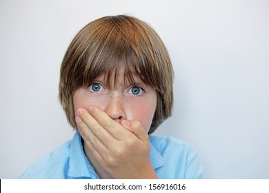 Young boy with hand over mouth in surprised or shocked expression