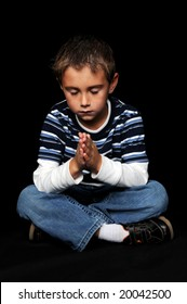Young boy with hands together praying