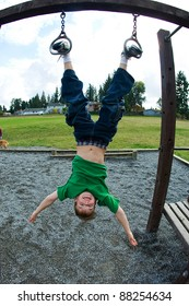 Young boy hanging upside down by his feet at a playground.
