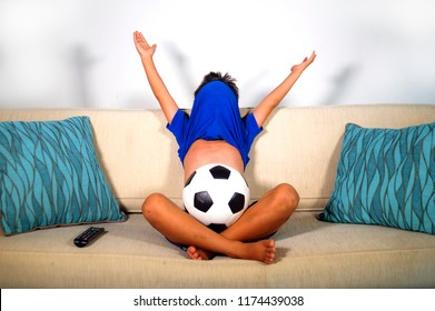 young boy happy and excited watching football game on television with ball at home living room couch alone celebrating scoring goal covering head with jersey as kid soccer little crazy fan
