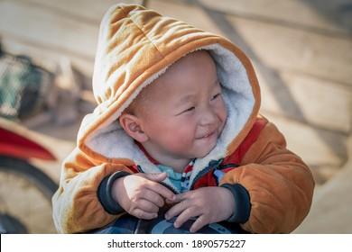Junge Junge, glücklicher junger Mann, im Winter Portrait mit Pulater, unscharfer Hintergrund, asiatischer Babyjunge
