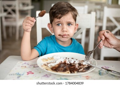 The young boy has a bad appetite, his mother has to feed him, he doesn't even want to eat dessert in cafe, the boy is tired after a long walk