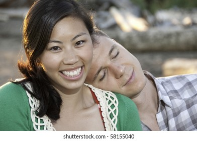 Young boy has his head on a chinese girls shoulder. She has a large smile.