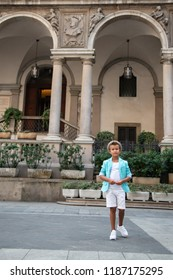 Young boy in hat posing in the milanese streets. Cute happy 6 years old boy posing in Milan, Italy. Kid's outdoor portrait, kid's street fashion. Trendy boy in suit in the Italian capital of fashion.
