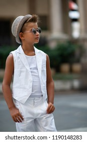 Young boy in hat posing and sun glasses in the milanese streets. Cute happy 6 years old boy posing in Milan, Italy. Kid's street fashion. Trendy boy in suit walking in the Italian capital of fashion.