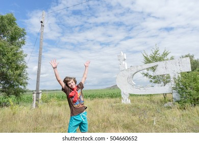 a young boy having fun jumping in a field.. the boy is in a rural location. boy standing on the road. boy stands near the stele time of the USSR. boy in shorts. red scarf around his neck. pioneer USSR