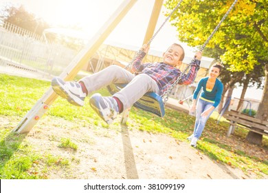 Young boy having fun on the swing. His mother or babysitter his swinging him and they are both enjoying it. Happy family and childhood lifestyle.