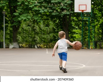Young boy having fun playing basketball outdoors