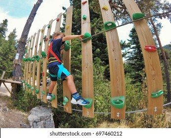 A young boy having fun at a treetop adventure park with ropes and climbing course. Rounded picture.