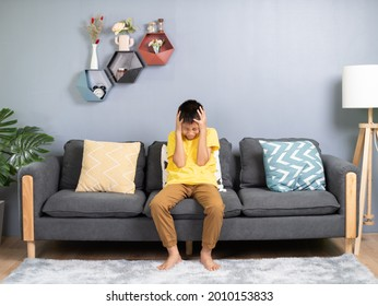 Young boy with headache holding his head in the room.