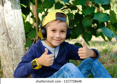 Young boy in headphones listening to modern music in nature. Child likes the song. Kid shows a thumbs up.