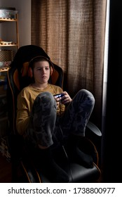 Young boy with headphones sitting in computer chair playing online games with controller in his hands
