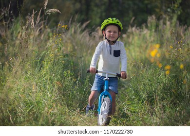 Young boy in helmet on balance bike riding on forest road