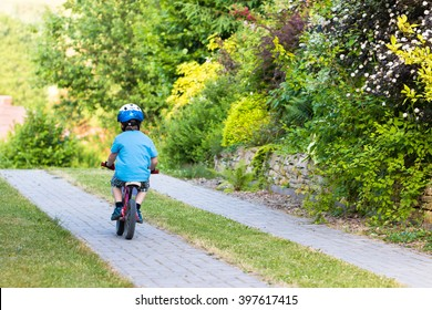 young boy with helmet riding his first balance bike in the backyard garden