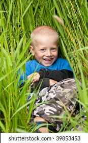 young boy hides in tall green grass and smiles