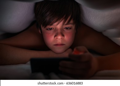 Young boy hiding under the blanket using his phone at night time - closeup