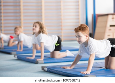 Young boy and his classmates on a gym mat focused on learning a cow yoga pose with arched back which helps with postural defects prevention