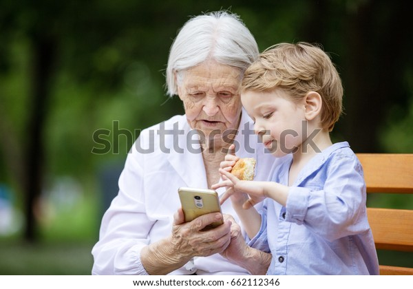 Young boy and his great grandmother using smartphone while sitting on bench in park